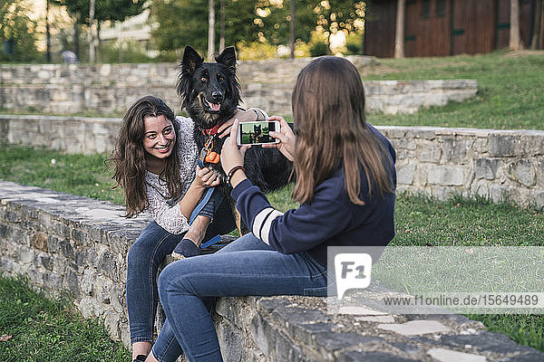 Schwestern fotografieren mit Hund im Park