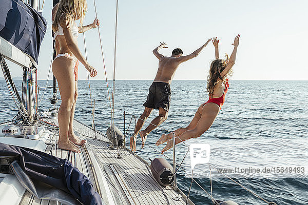 Friends jumping off sailboat into sea  Italy