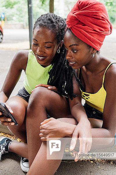 Freunde lesen Textnachricht auf Smartphone in der Stadt
