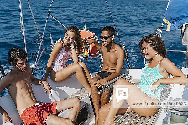 Freunde entspannen sich auf einem Segelboot  Italien