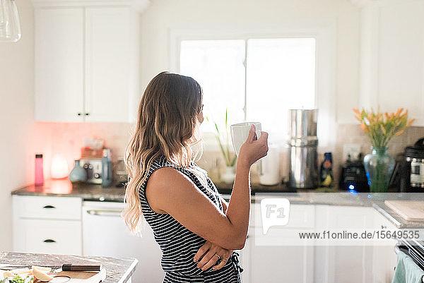 Frau genießt eine Tasse Heißgetränk in der Küche