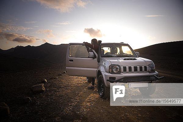 Reisende  die neben dem Fahrzeug eine malerische Aussicht genießt  Landmannalaugar  Hochland  Island