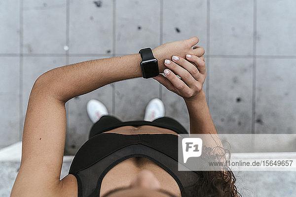 Junge Frau kontrolliert Smartwatch im Freien