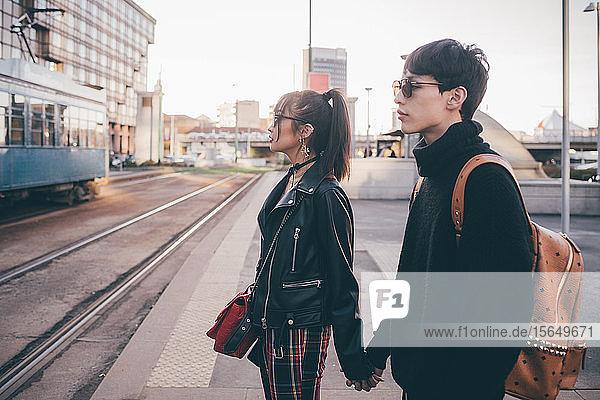 Junges Paar  das an den Straßenbahnschienen Händchen hält und wartet  Mailand  Italien