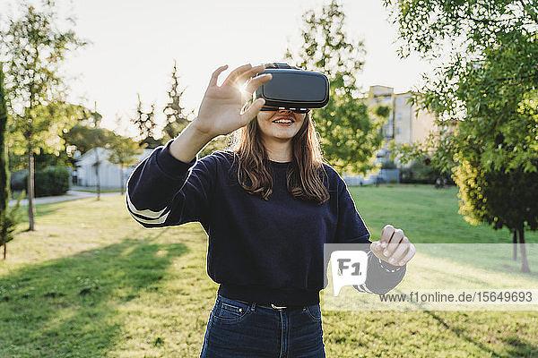 Junge Frau schaut durch VR-Headset im Park
