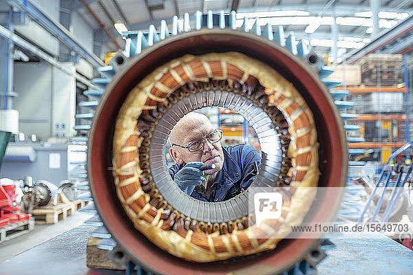 Elektroingenieur inspiziert Wicklung am Generator-Stator in elektrotechnischer Fabrik