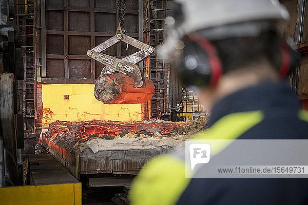 Stahlarbeiter beobachtet  wie rotglühende Stahlblöcke in Stahlwerken aus dem Ofen gehoben werden