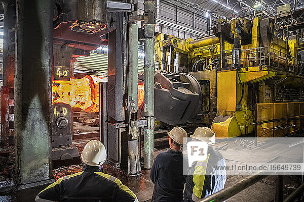 Steelworkers inspecting red hot steel ingot in heavy press in steelworks