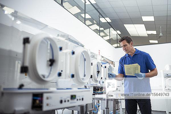 Arbeiter inspiziert Laborschrankmaschinen an der Produktionslinie in einer Fabrik für medizinische Wissenschaft