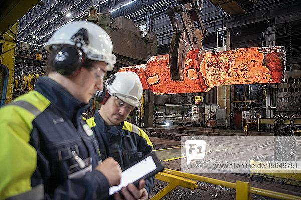 Stahlarbeiter machen Notizen auf digitaler Tafel durch rotglühenden Stahlblock in der Schmiede im Stahlwerk