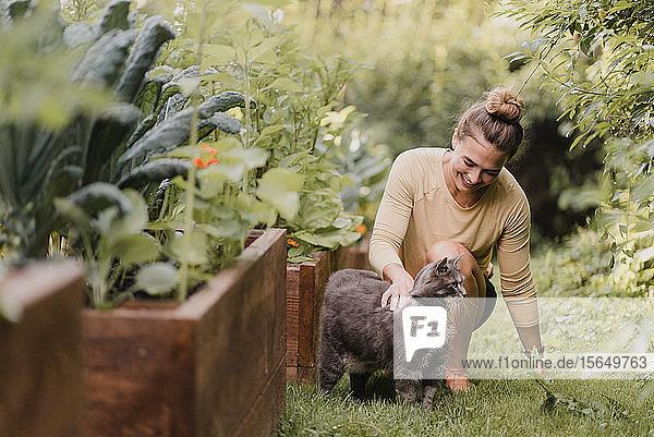 Gärtnerin mit Katze im Garten