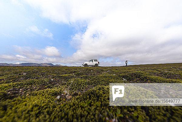 Wanderer erkundet moosbewachsene Landschaft  Landmannalaugar  Hochland  Island