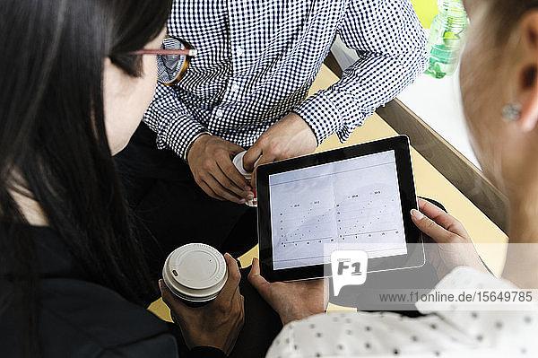 Geschäftsmann und Geschäftsfrauen verwenden digitales Tablet bei Besprechung im Büro