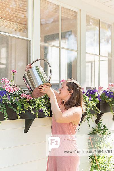Frau gießt Blumen im Garten