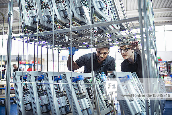 Workers with electronic parts on racks in electronics assembly factory
