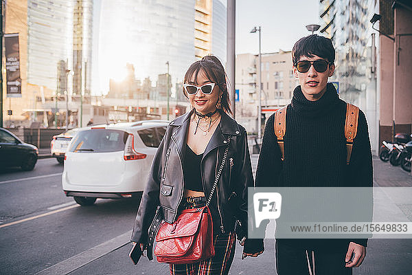 Young couple walking and holding hands on street  Milan  Italy