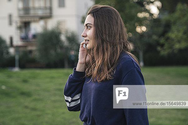 Junge Frau benutzt Smartphone im Park