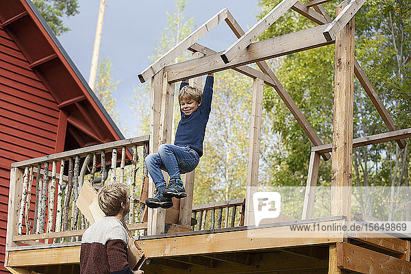 Father watching boy swinging on beam of unfinished treehouse