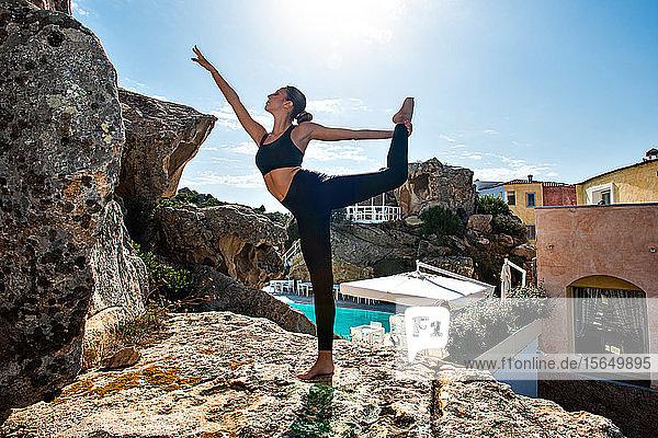 Frau praktiziert Yoga in der Nähe des Pools  Insel La Maddalena  Sardinien  Italien