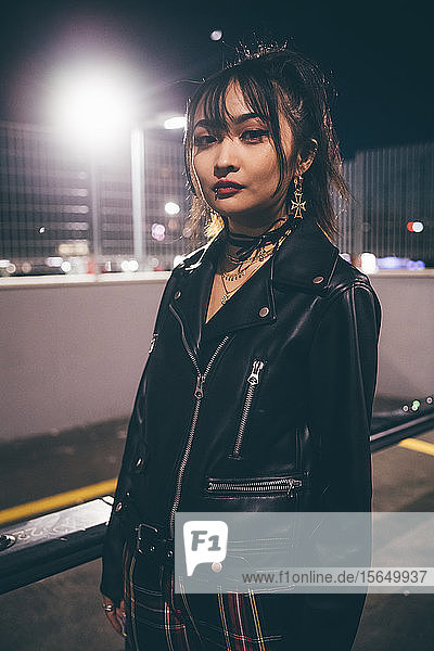 Woman beside railing  fencing and floodlights in background  Milan  Italy