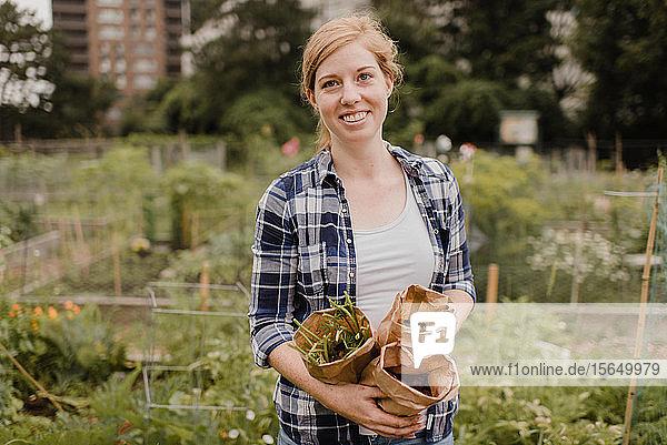 Frau trägt braune Säcke mit Gemüse im Schrebergarten