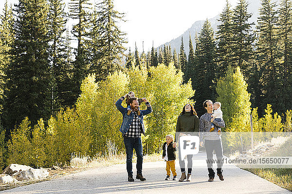 Family and friends on road through forest