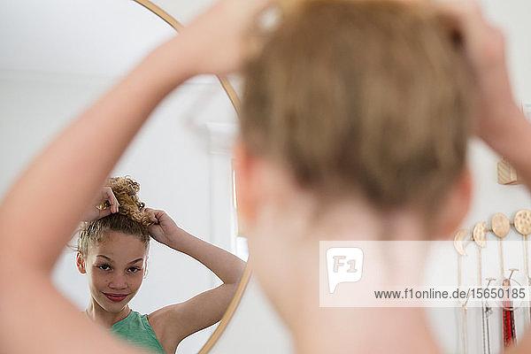 Mädchen macht Haare im Spiegel