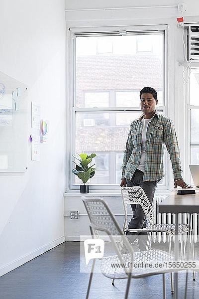 Geschäftsmann lehnt sich an Schreibtisch neben Whiteboard