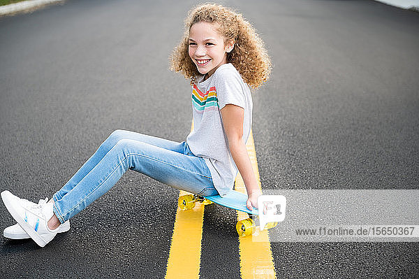 Mädchen sitzt auf Skateboard auf der Straße