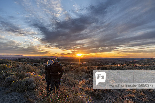 Couple in field at sunset at Boise Foothills in Boise  Idaho  USA