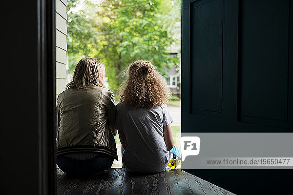 Mutter und Tochter sitzen auf der Veranda