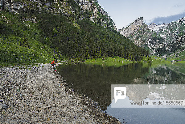 Woman crouching by Seealpsee lake in Appenzell Alps  Switzerland