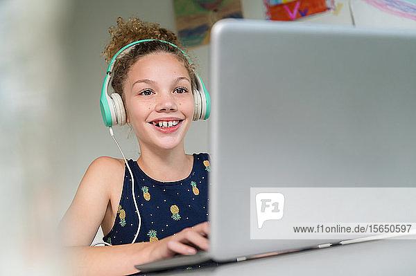Lächelndes Mädchen mit Kopfhörern und Laptop