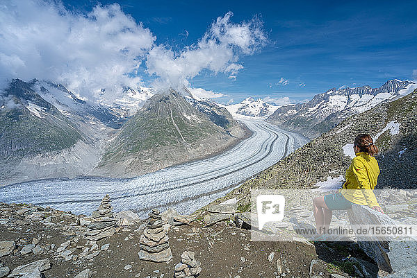 Side view of woman sitting on rocks admiring Aletsch Glacier from Eggishorn viewpoint  Bernese Alps  canton Valais  Switzerland