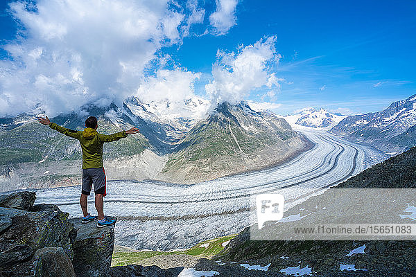 Man exulting with outstretched arms looking at Aletsch Glacier from Eggishorn viewpoint  Bernese Alps  canton of Valais  Switzerland