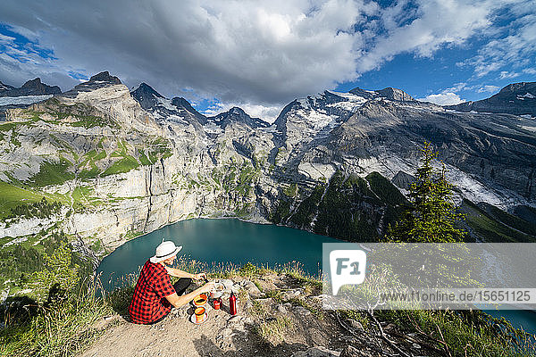 Hiker cooking food on camping stove high up above Oeschinensee lake  Bernese Oberland  Kandersteg  Canton of Bern  Switzerland