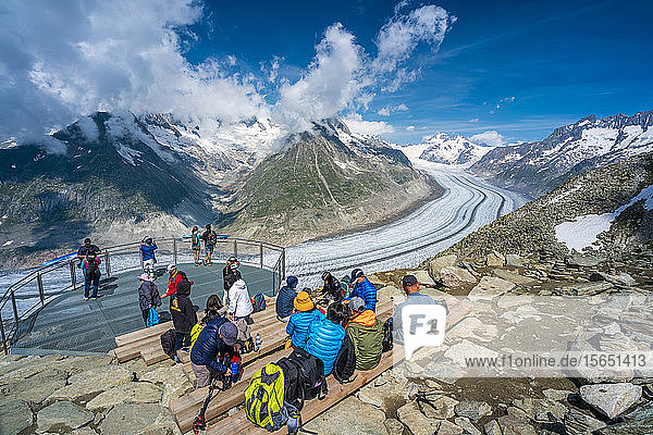 People admiring the majestic Aletsch Glacier from terrace at Eggishorn viewpoint  Bernese Alps  canton of Valais  Switzerland