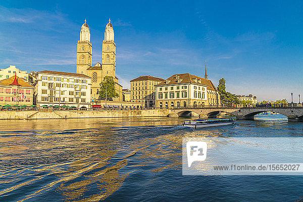 Ferry along Limmat River next to Munsterbrucke bridge with Grossmunster in background  Zurich  Switzerland
