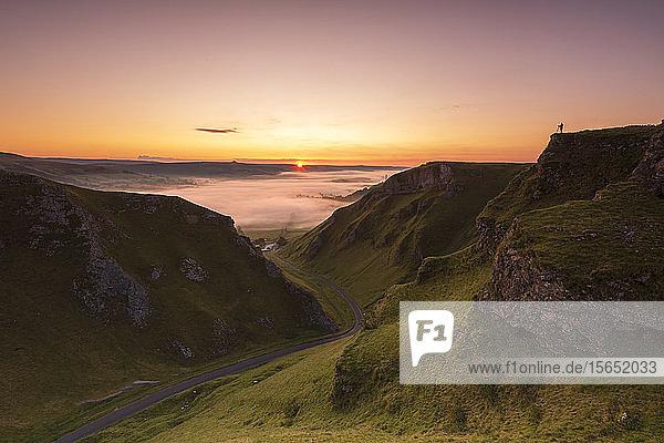 A photographer at Winnats Pass at sunrise  Hope Valley  Edale  Peak District  Derbyshire  England  United Kingdom