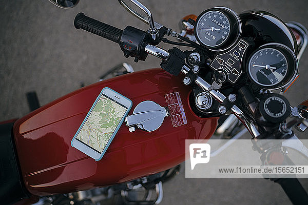 Smartphone with road map lying on tank of vintage motorbike  top view
