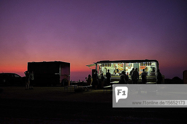 Portugal  Algarve  Purple sky over silhouettes of people relaxing at concession stand in Cape Saint Vincent at dawn