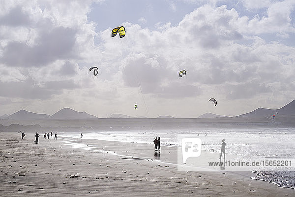 Spain  Canary Islands  Caleta de Famara  Silhouettes of people walking and kiteboarding at Playa de Famara