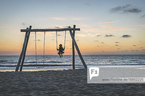 Netherlands  South Holland  Noordwijk  child on beach swing at sunset