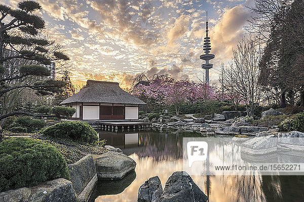 Scenic view of lake and house against cloudy sky in park during sunset at Hamburg  Germany
