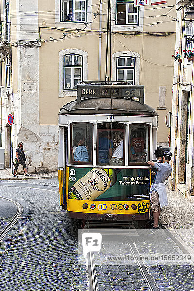 People riding on tram passing through residential district in Bairro Alto  Lisbon  Portugal