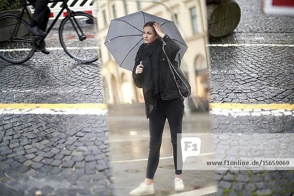 Young woman with umbrella looking at mirror on the street  Munich  Germany.