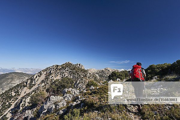 Woman with red backpack hiking near Pla de la Casa peak in Serrella mountain range  Confrides (province of Alicante  Valencian Community)