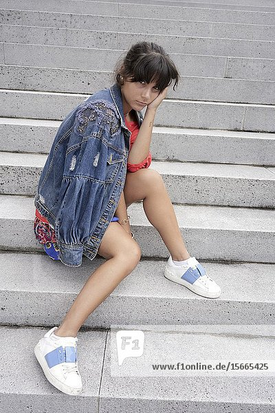Young woman sitting on steps.