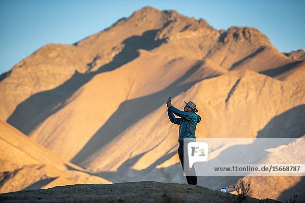 A tourist uses his cell phone to photograph the amazing views and scenery that the mountains of the Elqui Pisco Valley  Coquimbo  Chile.
