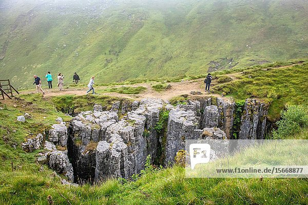 Tourists while hiking visit a natural rock crevice Hawes  Yorkshire  UK.